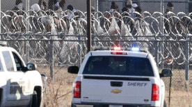 Prisoners burn objects as they mill in a courtyard behind razor wire at the Tecumseh State Correctional Institution in Tecumseh, Neb., Thursday, March 2, 2017. The prison has been placed on lockdown and inmates are refusing to return to their cells. Officials say approximately 40 inmates are involved in the disturbance. No injuries have been reported. (AP Photo/Nati Harnik)