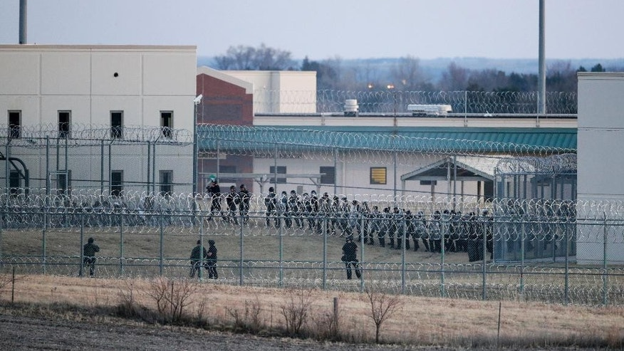 Security forces in riot gear surround a courtyard behind razor wire at the Tecumseh State Correctional Institution in Tecumseh, Neb., Thursday, March 2, 2017, where dozens inmates congregated after refusing to return to their cells. The prison was placed on lockdown for roughly three hours Thursday after inmates in a housing unit refused to return to their cells and a fire was started in a yard. (AP Photo/Nati Harnik)