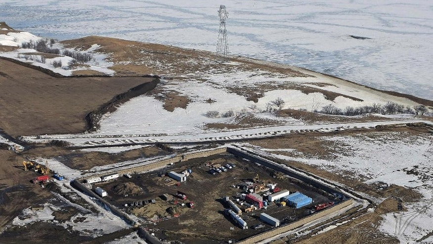 FILE - In this Feb. 13, 2017, aerial file photo shows the site where the final phase of the Dakota Access Pipeline will take place with boring equipment routing the pipeline underground and across Lake Oahe to connect with the existing pipeline in Emmons County near Cannon Ball, N.D. An Associated Press analysis shows North Dakota stands to gain more than $110 million annually in tax revenue after oil begins coursing through the pipeline. (Tom Stromme/The Bismarck Tribune via AP, File)