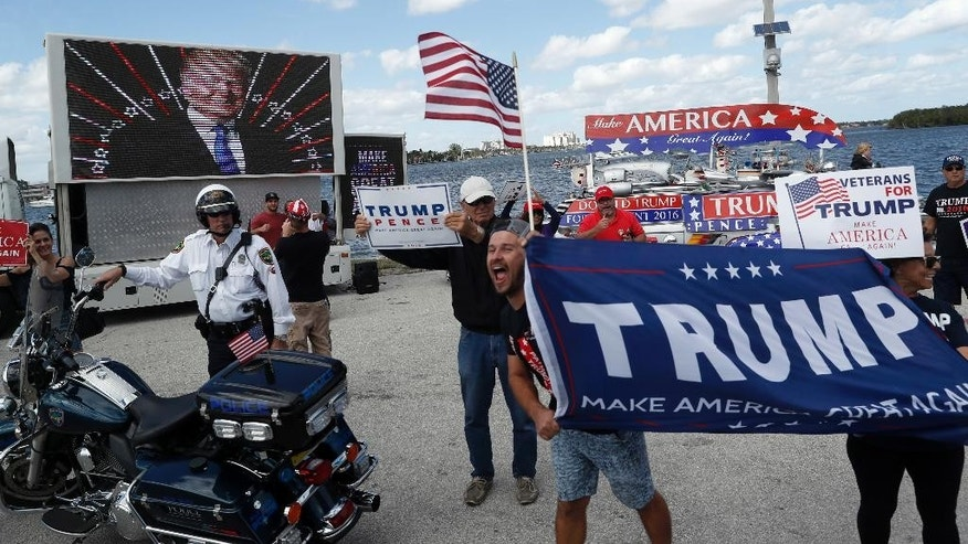 Supporters of President Donald Trump gather outside Mar-a-Lago, Saturday, March 4, 2017, in Palm Beach, Fla. (AP Photo/Alex Brandon)