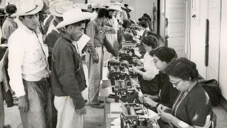 This undated photo provided by the United States Citizenship and Immigration Services' (USCIS) History Library and the National Trust for Historic Preservation, shows temporary clerks completing the short-term labor contracts and identification cards. Each clerk was proficient in both Spanish and English. The bracero program is the largest guest-worker program in our nation's history and recruited 4.6 million skilled Mexican nationals. (United States Citizenship and Immigration Services' (USCIS) History Library/National Trust for Historic Preservation via AP)