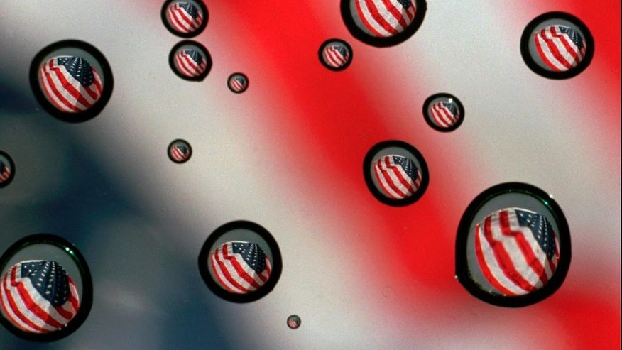 In this Nov. 10, 1997 file photo,a  U.S. flag refracted in water drops on a car windshield in Gorham, Maine. The vast majority of Americans fear the country is losing its identity, but underlying that widespread agreement is equally deep disagreement over what it means to be an American. A new poll from The Associated Press-NORC Center for Public Affairs Research finds the country is torn over what poses the greatest threat to the national way of life.  (AP Photo/Carl D. Walsh)