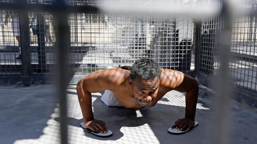 FILE - In this Aug. 16, 2016 file photo, condemned inmate Donald DeBose does pushups in a caged recreation yard space of the adjustment center on death row at San Quentin State Prison in San Quentin, Calif. A settlement of a lawsuit by inmates against the state of California, obtained by The Associated Press, says the state no longer will keep inmates in the center just for being gang members. Inmates can still be sent to the windowless cells if they are considered an immediate danger. (AP Photo/Eric Risberg, File)
