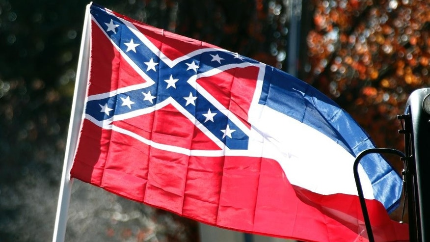 "FILE - In this Tuesday, Jan. 19, 2016 file photo, a state flag of Mississippi is unfurled by Sons of Confederate Veterans and other groups on the grounds of the state Capitol in Jackson, Miss. A long-running feud over the Confederate battle emblem on the Mississippi flag is moving onto a new legal battlefield. The 5th U.S. Circuit Court of Appeals in New Orleans is scheduled to hear arguments Tuesday, March 7, 2017, over reviving a 2016 lawsuit filed by an African-American attorney, Carlos Moore. He contends the flag is ""state-sanctioned hate speech."" (AP Photo/Rogelio V. Solis, File)"
