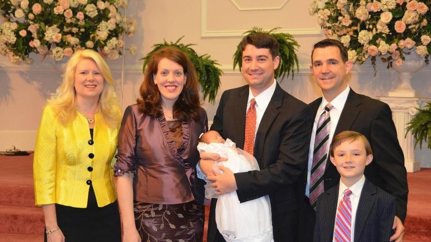 In this 2012 photo provided by a former member of the church, Jeffrey Cooper holds his infant daughter at her 2012 baby dedication at the Word of Faith Fellowship compound in Spindale, N.C. At second right is Frank Webster, an assistant North Carolina prosecutor who is married to church leader Jane Whaley's daughter, Robin, left. At right is Frank Webster's son, Brock. At second left is Jeffrey Coopers' wife, Natalie. Frank Webster and Chris Back _ church ministers who handle criminal cases as assistant DAs for three nearby counties _ provided legal advice, helped at strategy sessions and participated in a mock trial for four congregants charged with harassing a former member, according to former congregants interviewed as part of an AP investigation of Word of Faith. (AP Photo)