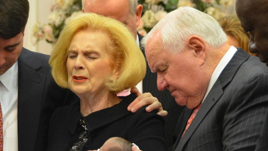 In this 2012 provided by a former member of the church, Word of Faith Fellowship leader Jane Whaley, center left, holds Jeffrey Cooper's infant daughter, accompanied by her husband, Sam, center right, and others during a ceremony in the church's compound in Spindale, N.C. At least a half-dozen times over two decades, authorities investigated reports that members of a secretive evangelical church were being beaten. And every time, according to former congregants, the orders came down from church leaders: They must lie to protect the sect. (AP Photo)