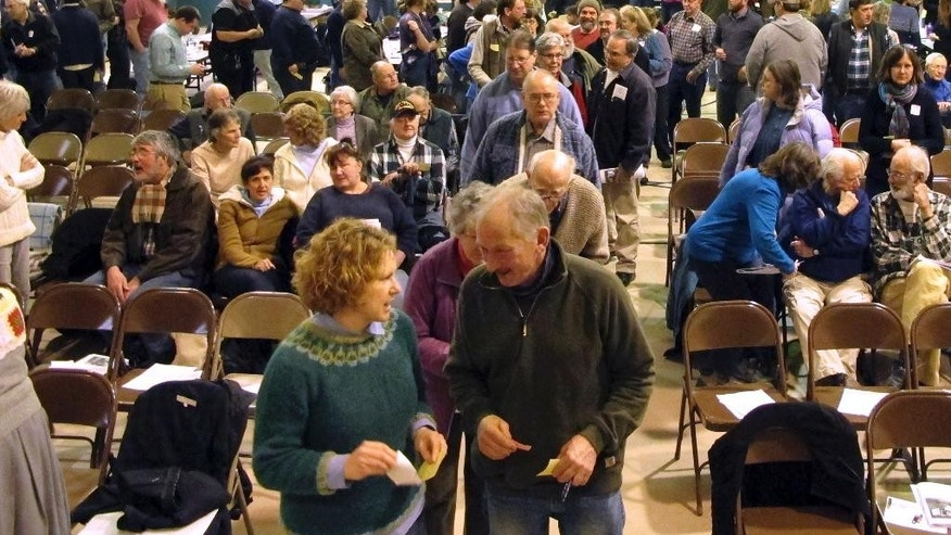 Residents line up to vote at the annual Town Meeting Tuesday, March 7, 2017, in Tunbridge, Vt. The town voted overwhelming against a large-scale development by a Utah businessman that would be based on the papers of Mormon leader Joseph Smith. (AP Photo/Lisa Rathke)