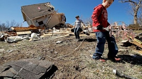 Kadin Lance, right, and his brother Carter Lance pick up debris at a friend's destroyed home Tuesday, March 7, 2017, after a tornado damaged tore through Oak Grove, Mo., Monday night. (AP Photo/Charlie Riedel)
