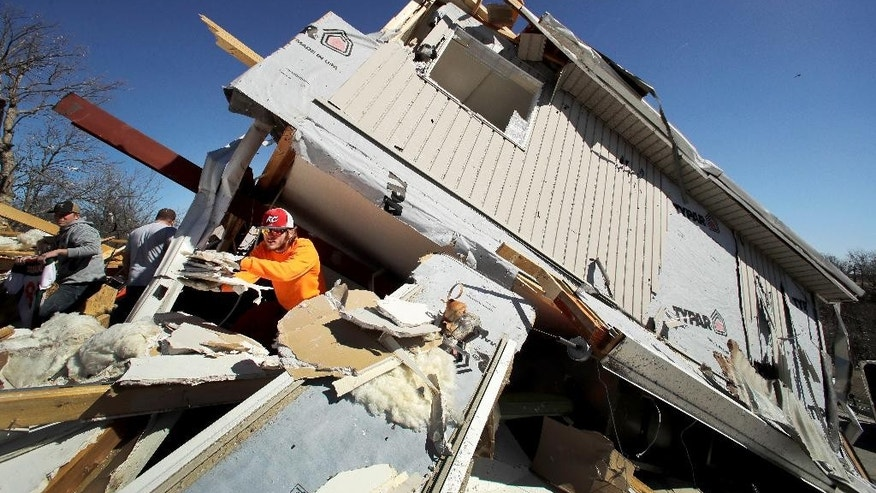 Skyler Jackson salvages items from a friend's destroyed home Tuesday, March 7, 2017, after a tornado tore through Oak Grove, Mo., Monday night. (AP Photo/Charlie Riedel)