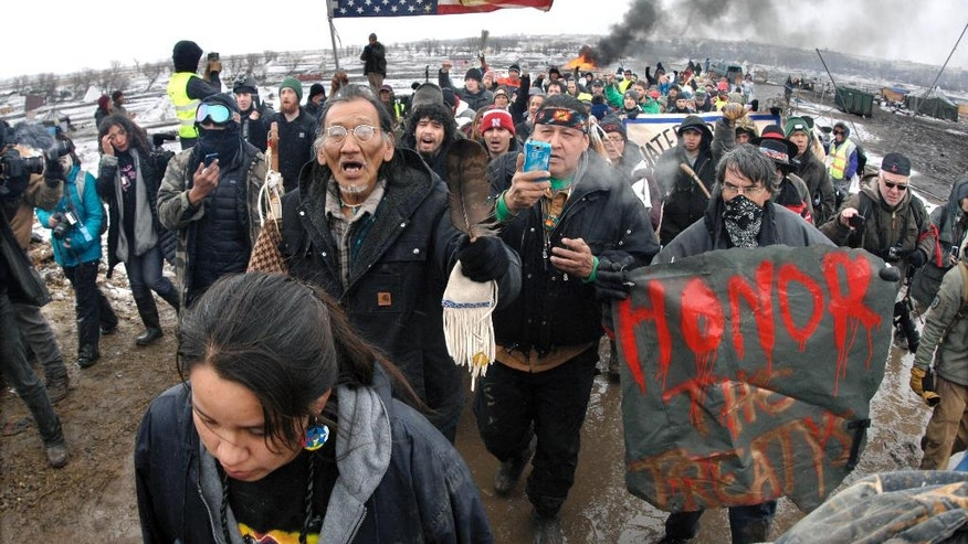 FILE - In this  Feb. 22, 2017, file photo, a large crowd representing a majority of the remaining Dakota Access Pipeline protesters march out of the Oceti Sakowin camp before the 2 p.m. local time deadline set for evacuation of the camp mandated by the U.S. Army Corps of Engineers near Cannon Ball, N.D. American Indians from across the country are bringing their frustrations with the Trump administration and its approval of the Dakota Access oil pipeline to the nation's capital Tuesday, March 7, 2017, kicking off four days of activities that will culminate in a march on the White House.  (Mike McCleary/The Bismarck Tribune via AP, File)