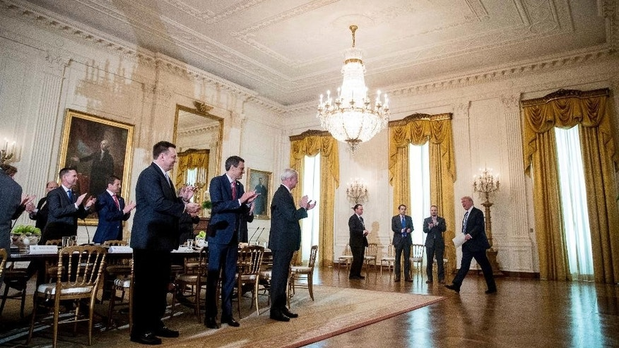 President Donald Trump is applauded as he arrives in the East Room of the White House in Washington, Tuesday, March 7, 2017, for a meeting with the House Deputy Whip team. (AP Photo/Andrew Harnik)
