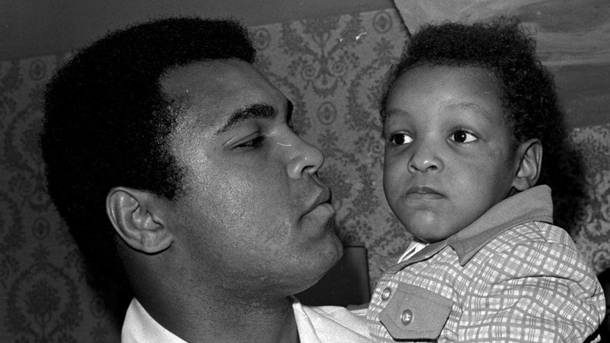 FILE - In this April 15, 1975 file photo, heavyweight boxing champion Muhammad Ali, and Little Muhammad Ali, his 2-and-a-half year old son, arrive at Miami Beach, Fla. Muhammad Ali's son, who bears his name, is launching a campaign in support of religious freedom a month after he and his mother were detained by immigration officials at a Florida airport. Ali Jr. said he was questioned about his religion during the incident, which showed him that work remains around his father's fight on the issue.  (AP Photo/File)