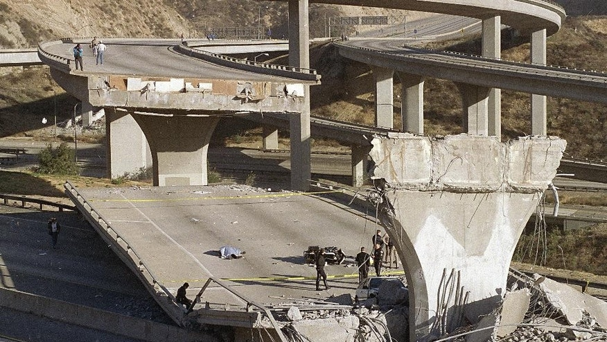 FILE - In this Jan. 17, 1994, file photo, the covered body of Los Angeles Police Officer Clarence Wayne Dean, 46, lies near his motorcycle which plunged off the State Highway 14 overpass that collapsed onto Interstate 5, after a magnitude-6.7 Northridge earthquake in Los Angeles. A new study says an earthquake fault running from San Diego to Los Angeles is capable of producing a magnitude-7.4 temblor that could affect some of the most densely populated areas in California. (AP Photo/Doug Pizac, File)