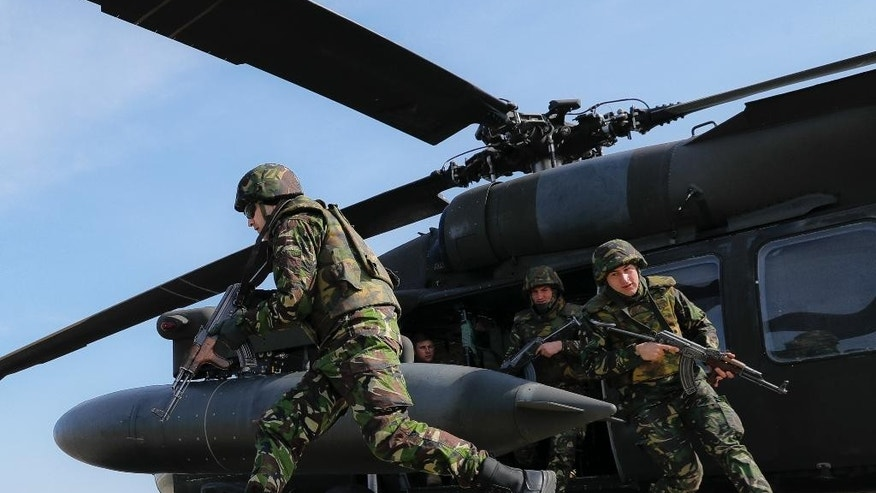 Romanian servicemen run out of an US Army 2nd Battalion, 10th Regiment, 10th Brigade UH-60 Blackhawk helicopter during a joint US-Romanian air assault exercise at the Mihail Kogalniceanu airbase, eastern Romania, Wednesday, March 8, 2017. Romanian and U.S troops are staging joint exercises with U.S. Black Hawk helicopters, part of the 10th Combat Aviation Brigade nine-month rotational deployment in support of Operation Atlantic Resolve, which aims to reassure NATO's European allies in light of Russia's invasion in Ukraine. (AP Photo/Vadim Ghirda)