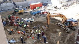Workers excavate coffins from a construction site in the Old City neighborhood, Thursday, March 9, 2017, in Philadelphia. Crews working on an apartment building in Philadelphia's historic district got a shock last month when their backhoes started hitting coffins and unearthing fully intact human remains. The site was supposed to be a former burial ground from 1707, and all remains were supposedly exhumed in the 1800s and moved to a different cemetery. (AP Photo/Matt Slocum)