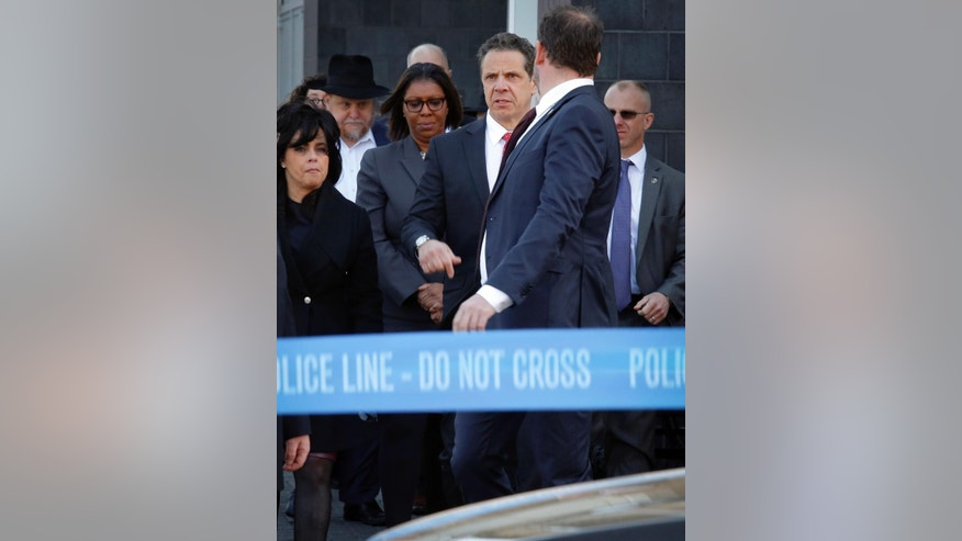 New York Gov. Andrew Cuomo, third from right, and Public Advocate Letitia James, center, meet with local Jewish leaders at the Jewish Children's Museum following a bomb threat, Thursday March 9, 2017 in Brooklyn borough of New York.   New York City's head of police intelligence says investigators believe one person is behind a large number of the threats made against U.S. Jewish institutions this year.  (AP Photo/Bebeto Matthews)