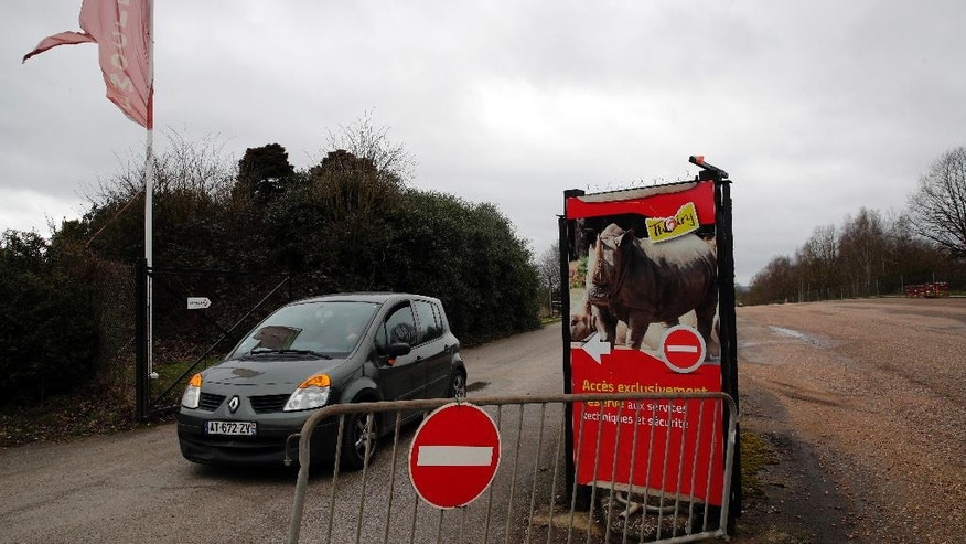 A car leaves the Thoiry Zoo, near Paris, France, Wednesday, March 8, 2017, where a rhinoceros named Vince was killed and one of it's horns removed using a chain saw. A zoo director says a 5-year-old rhinoceros at the wildlife park he runs near Paris, had been shot three times in the head by assailants who stole the animal's horn, it's carcass being found Tuesday. (AP Photo/Christophe Ena)