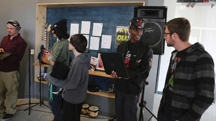 Hip Hop artist James Laurie of The Flobots, co-founder of Youth on Record, talks with music student Dante Hicks at the nonprofit in 2014.
