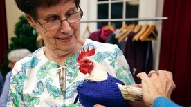 "In this Wednesday, March 8, 2017 photo Nancy Kearns, as resident of Fuller Village retirement home holds ""Prince Peep,"" a rooster native to Malaysia, as the bird is fitted with a sweater at the retirement home in Milton, Mass. Sweaters for chickens? It sounds like a joke, but a plucky group of retirees in suburban Boston has hatched a plan to keep poultry warm during the New England winter. Kearns said the project benefits birds kept on a neighboring estate known as the Mary M.B. Wakefield Charitable Trust. (AP Photo/Steven Senne)"