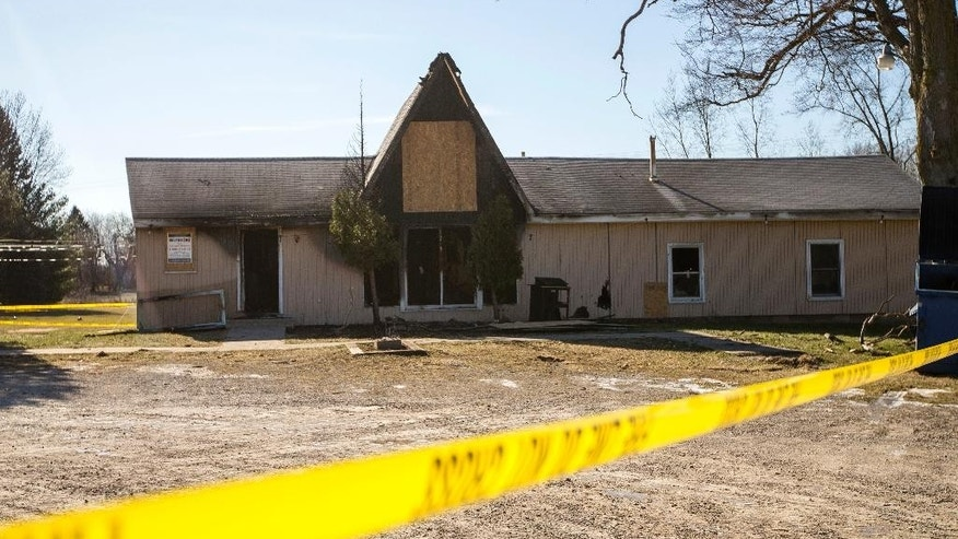 In this Sunday, March 12, 2017 photo, police tape surrounds the Islamic Center of Ypsilanti which caught fire Saturday, March 11 in Ypsilanti, Mich. Authorities said they've identified a 16-year-old boy as a suspect in the fire that destroyed the mosque.   (Matt Weigand /The Ann Arbor News via AP)