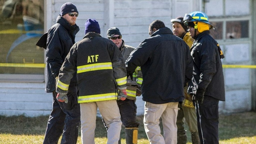 In this Saturday, March 11, 2017 photo, ATF police officers gather to talk outside of the Islamic Center of Ypsilanti, which caught fire, in Ypsilanti, Mich. Authorities said they've identified a 16-year-old boy as a suspect in the fire that destroyed the mosque.  (Matt Weigand /The Ann Arbor News via AP)