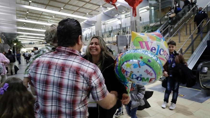Nadia Hanan Madalo, center, hugs her brother Gassan Kakooz at the airport after arriving from Iraq Wednesday, March 15, 2017, in San Diego. Madalo and her family, refugees forced to flee their town of Batnaya, Iraq, after the Islamic State invaded and destroyed it several years ago, arrived in San Diego to be reunited with Madalo's siblings and mother. As they flew to the U.S. on Wednesday, a federal judge in Hawaii put a hold on President Trump's newest ban - the latest development in a fight between the administration and the courts that has injected more uncertainty into the lives of refugees. (AP Photo/Gregory Bull)