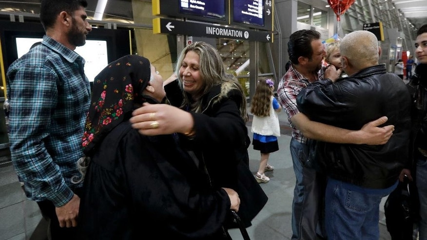 Nadia Hanan Madalo, center right, hugs her mother, Alyshooa Kannah, center left, at the airport after arriving from Iraq Wednesday, March 15, 2017, in San Diego. Madalo and her family, refugees forced to flee their town of Batnaya, Iraq, after the Islamic State invaded and destroyed it several years ago, arrived in San Diego to be reunited with Madalo's siblings and mother. As they flew to the U.S. on Wednesday, a federal judge in Hawaii put a hold on President Trump's newest ban - the latest development in a fight between the administration and the courts that has injected more uncertainty into the lives of refugees. (AP Photo/Gregory Bull)