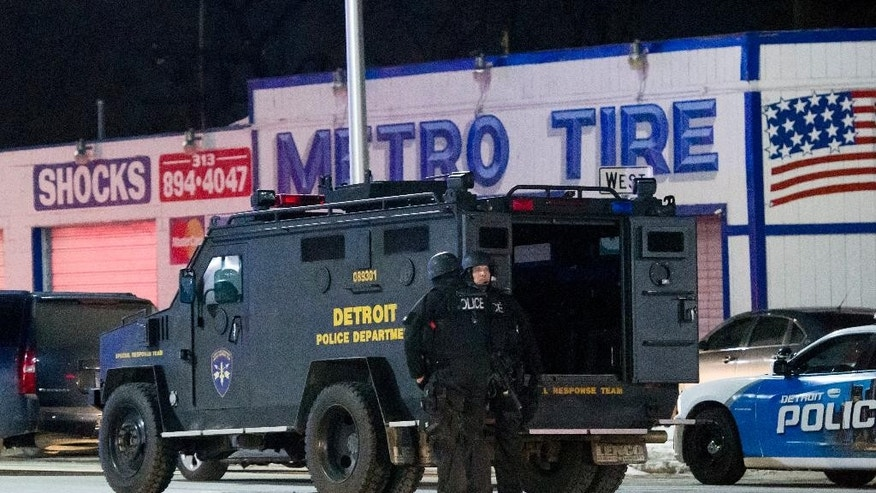 In a Wednesday, March 15, 2017 photo, Detroit police gather at the staging area near Ash and Tillman in Detroit for the search a suspect wanted in the shooting of two Detroit police officers. A 60-year-old man suspected in the shooting has been arrested and the officers are in stable condition, the police chief said Thursday. (David Guralnick/Detroit News via AP)