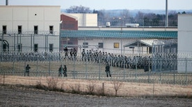 FILE - In this March 2, 2017, file photo, security forces in riot gear surround a courtyard behind razor wire at the Tecumseh State Correctional Institution in Tecumseh, Neb., where dozens inmates congregated after refusing to return to their cells. Authorities said inmates at the prison that erupted into violence earlier this month assaulted four staff members Wednesday, March 16, 2017. (AP Photo/Nati Harnik, File)