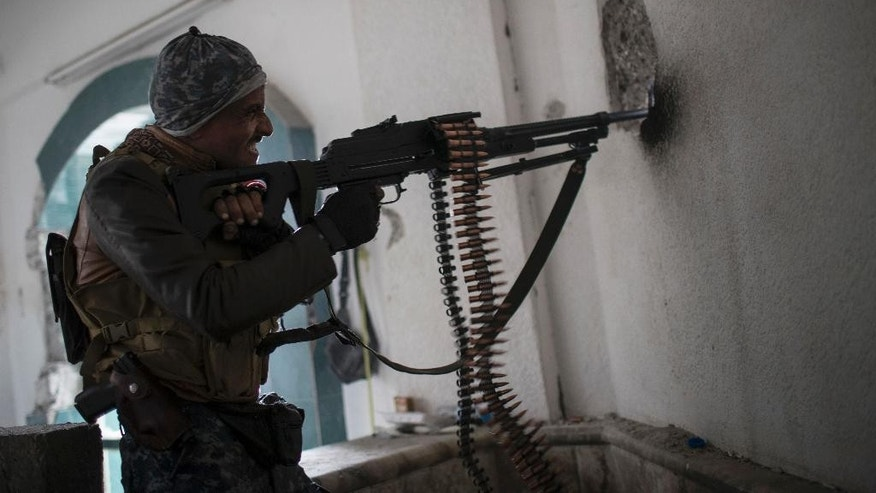 A Federal Police soldier shoots toward Islamic State militant positions during fighting in western Mosul, Iraq, Thursday, March 16, 2017. (AP Photo/Felipe Dana)