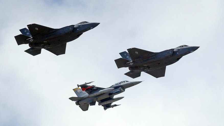 FILE - This Sept. 2, 2015 file photo shows an F-16, below, escorting two F-35 jets, above, after arriving the latter arrived at Hill Air Force Base in Utah. The U.S. and its Asia-Pacific allies are rolling out their new stealth fighter jet, a cutting-edge plane that costs about $100 million each. (AP Photo/Rick Bowmer, File)