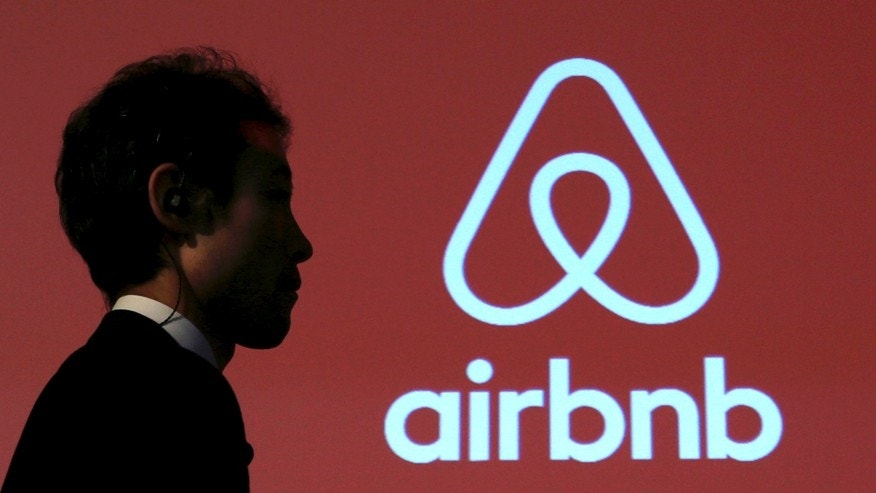 A man walks past a logo of Airbnb.