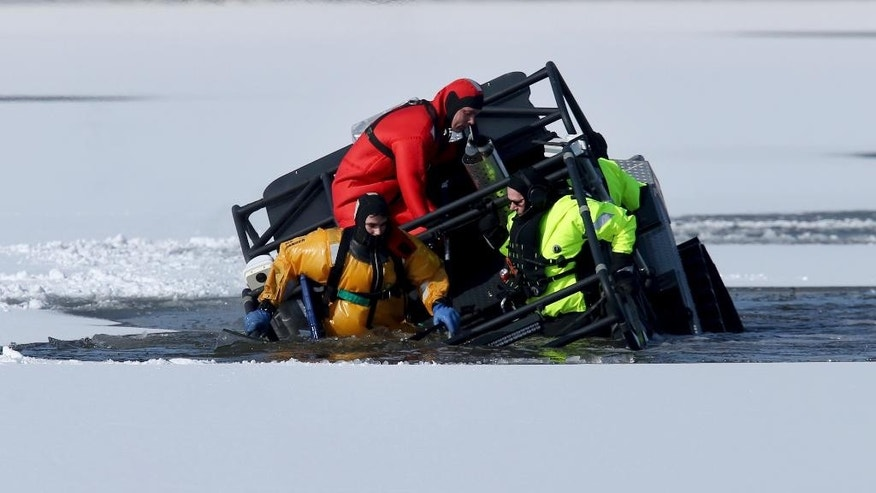An amphibious vehicle sinks with rescue personnel on board Sunday, March 19, 2017, as they try to retrieve a deer that was stuck on ice for more than 12 hours on a pond in Roxbury, NJ. No one was hurt, and all five on the vehicle were rescued along with the deer. (Ed Murray/NJ Advance Media via AP)