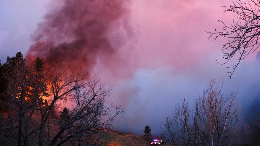 Smoke rises from a wildfire Sunday, March 19, 2017, in Boulder, Colo. Authorities said the small wildfire burning in the mountains forced people from their homes and is filling the sky with smoke. (Seth Frankel via AP)