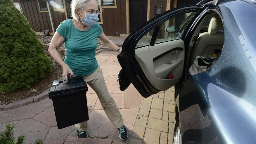 Anne Slichter prepares to evacuate her home near the Sunshine Fire near Boulder Canyon west of Boulder, Colo., on Sunday, March 19, 2017.  The fire forced people from their homes early Sunday and ignited dead trees that exploded into black plumes of smoke, authorities and residents said.  (Paul Aiken/Daily Camera via AP)