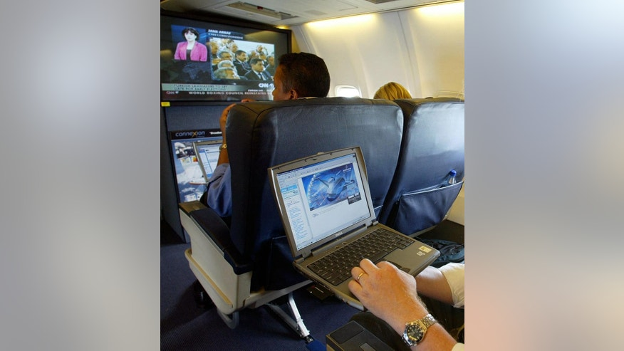FILE - This is a  July 29, 2002  file photo of  a laptop is used on a plane . Britain's government  Tuesday March 21, 2017 banned electronic devices in the carry-on bags of passengers traveling to the U.K. from six countries, following closely on a similar ban imposed by the United States. (Chris Ison/PA, File via AP)