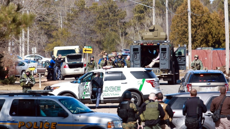 Numerous law enforcement vehicles and SWAT teams respond to shooter Wednesday, March 22, 2017, at an apartment complex in Rothschild, Wis.