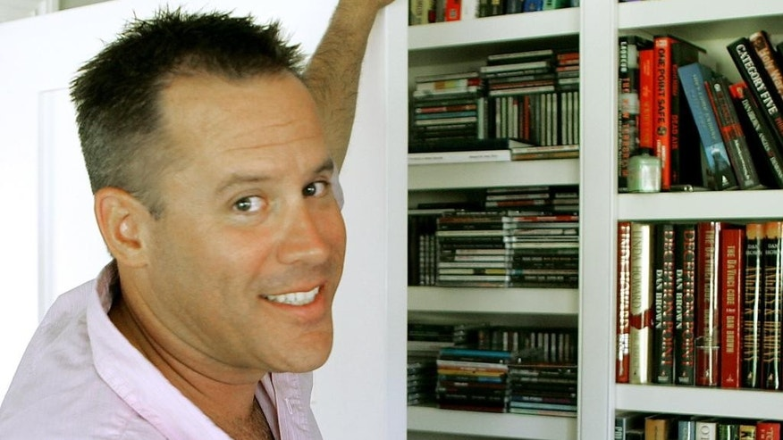 "FILE - This Sept. 2, 2005 file photo shows best-selling author Vince Flynn in the library of his Edina, Minn. home.  The late Minnesota author's counterterrorism operative Mitch Rapp is coming to the big screen in September. CBS Films and Lionsgate announced Wednesday, March 22, 2017 that ""American Assassin,"" based in Flynn's best-seller, will hit theaters nationwide and in North America on Sept. 15. Flynn wrote a series of thrillers featuring Rapp. He died in 2013 after battling prostate cancer.  (AP Photo/Jim Mone)"