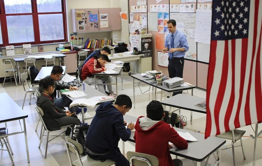 "In this Feb. 15, 2017, photo, Eric Hoover teaches his class of immigrant and refugee students at McCaskey High School in Lancaster, Pa. The Lancaster community runs an ""international school"" on its main high school campus to help the waves of new arrivals sponsored by local resettlement agencies learn English and adjust to American schools. (AP Photo/Michael Rubinkam)"