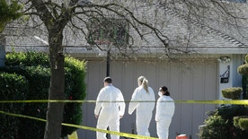 Investigators walk to the home where four people were found dead, Thursday, March 23, 2017, in Sacramento, Calif. A suspect is being held in San Francisco. Police are not saying how the four were killed and are not immediately identifying the victims, including their genders and ages. (AP Photo/Rich Pedroncelli)
