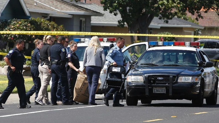 A Sacramento City Police officer, center, carries a bag that was brought from the home where four people were found dead, Thursday, March 23, 2017, in Sacramento, Calif. A suspect is being held in San Francisco. Police are not saying how the four were killed and are not identifying the victims, including their genders and ages. (AP Photo/Rich Pedroncelli)