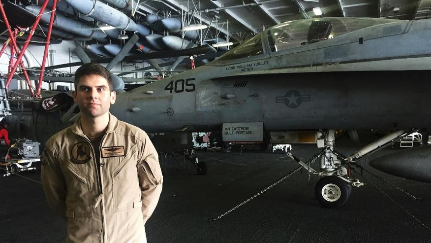 In this Wednesday, March 22, 2017 photograph, Lt. Cmdr. William Vuillet speaks to The Associated Press on board the USS George H.W. Bush as it travels through the Persian Gulf. The carrier soon will begin launching airstrikes targeting the Islamic State group in Iraq and Syria. Vuillet spoke to the AP about the challenges of launching those strikes. (AP Photo/Jon Gambrell)