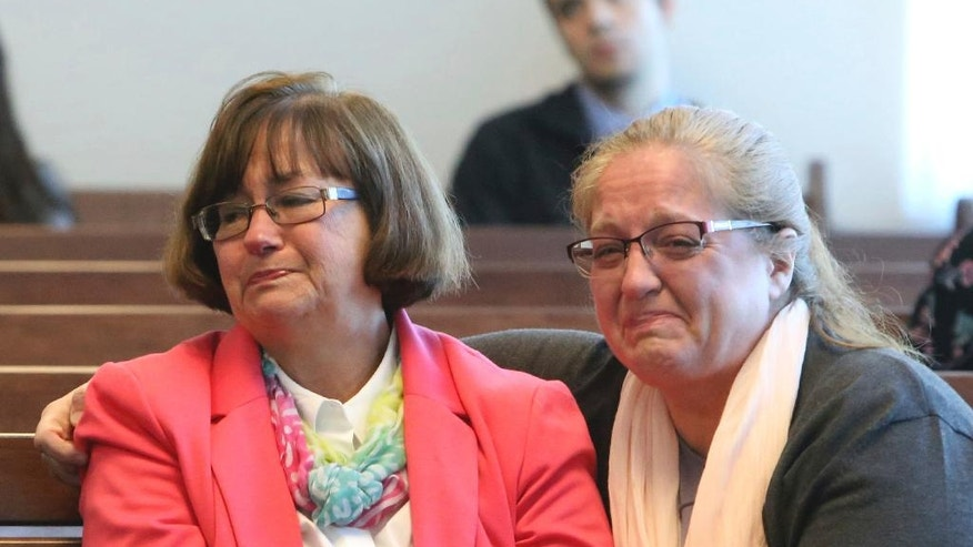 Carole Gustafson, left, second wife of Andrew Gustafson, and unidentified woman react in Middlesex Superior Court in Woburn, Mass., Thursday, March 23, 2017, as Danial LaPlante is resentenced to three consecutive life terms in the 1987 murders of Andrew's first wife Priscilla Gustafson and their children, Abigail and William, in Townsend, Mass.(Julia Malaki//The Lowell Sun via AP, Pool)