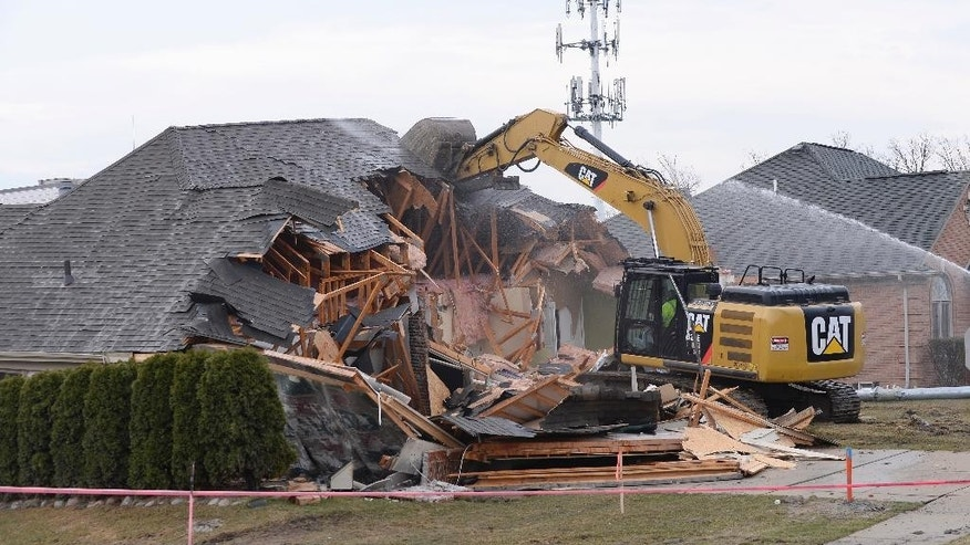 A house in Fraser, Mich. is demolished  to help clear the way for repairs to a broken sewer line that caused a sinkhole on Christmas Eve in suburban Detroit, on Friday, March 24, 2017.  Three houses had to be condemned in Fraser and a major road has been closed. Macomb County Public Works spokesman Dan Heaton says one of those homes was demolished on Friday and the other is expected to be torn down on Monday.  (Clarence Tabb Jr./Detroit News via AP)