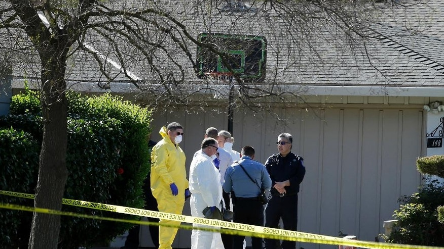 Investigators gather outside a home where four people were found dead, Thursday, March 23, 2017, in Sacramento, Calif. A suspect is being held in San Francisco. Police are not saying how the four were killed and are not immediately identifying the victims, including their genders and ages. (AP Photo/Rich Pedroncelli)
