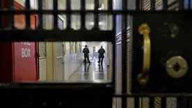 FILE - This Dec. 29, 2015 file photo shows guards walking a corridor in the death row adjustment center at San Quentin State Prison in San Quentin, Calif. A settlement of a lawsuit by inmates against the state of California, obtained by The Associated Press, says the state no longer will keep inmates in the center just for being gang members. Inmates can still be sent to the windowless cells if they are considered an immediate danger. (AP Photo/Ben Margot, File)