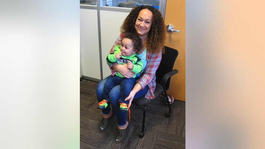 In this March 20, 2017 photo, Rachel Dolezal poses for a photo with her son, Langston in the bureau of the Associated Press in Spokane, Wash. Dolezal, who has legally changed her name to Nkechi Amare Diallo, rose to prominence as a black civil rights leader, but then lost her job when her parents exposed her as being white and is now struggling to make a living. (AP Photo/Nicholas K. Geranios)