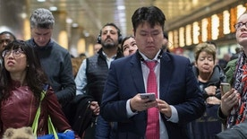 Evening rush hour commuters inspect the departures information board while they wait for their respective Long Island Rail Road trains at Penn Station, Friday, March 24, 2017, in New York. Commuters to both New Jersey and Long Island faced a difficult journey home Friday evening after two passenger trains clipped each other during the morning rush at Penn Station, jolting riders and creating major travel disruptions, but causing no serious injuries. (AP Photo/Mary Altaffer)
