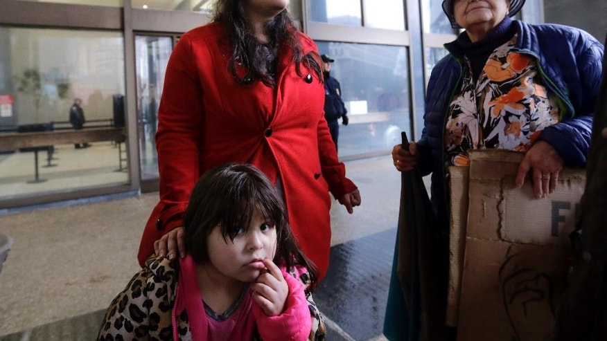 Lymarie Deida stands with her four-year-old daughter, Solmarie Carrillo, outside the JFK Federal Building, Monday, March 27, 2017, in Boston, where a bail hearing for her husband, Alex Carrillo, was to take place. Carrillo, an undocumented Vermont farm worker, and two advocates for Vermont dairy farm workers have been detained by federal immigration officials. (AP Photo/Elise Amendola)