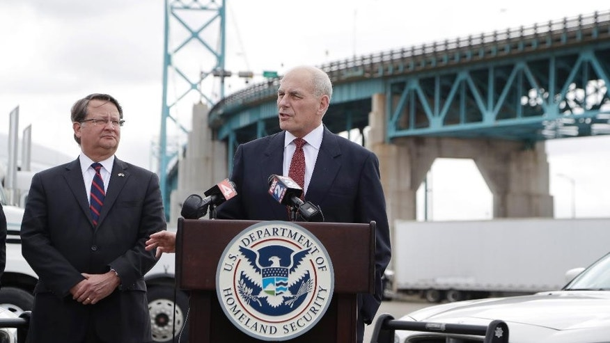 Homeland Security Secretary John Kelly, right, accompanied by Sen. Gary Peters D-Mich., speaks to the media at the Ambassador Bridge border crossing, Monday, March 27, 2017, in Detroit. Kelly observed northern border operations and met with DHS personnel, local immigration stakeholders and Arab American community members. (AP Photo/Carlos Osorio)